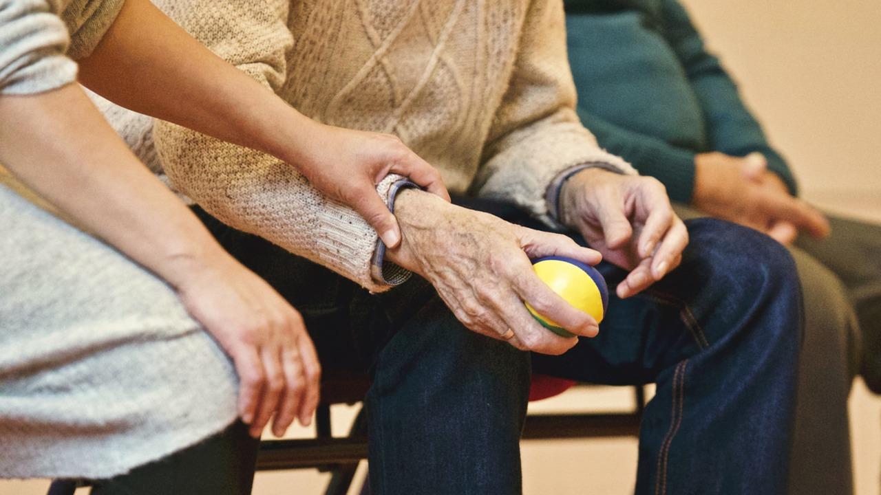 Main animatrice tenant le bras d'un monsieur âgé assis