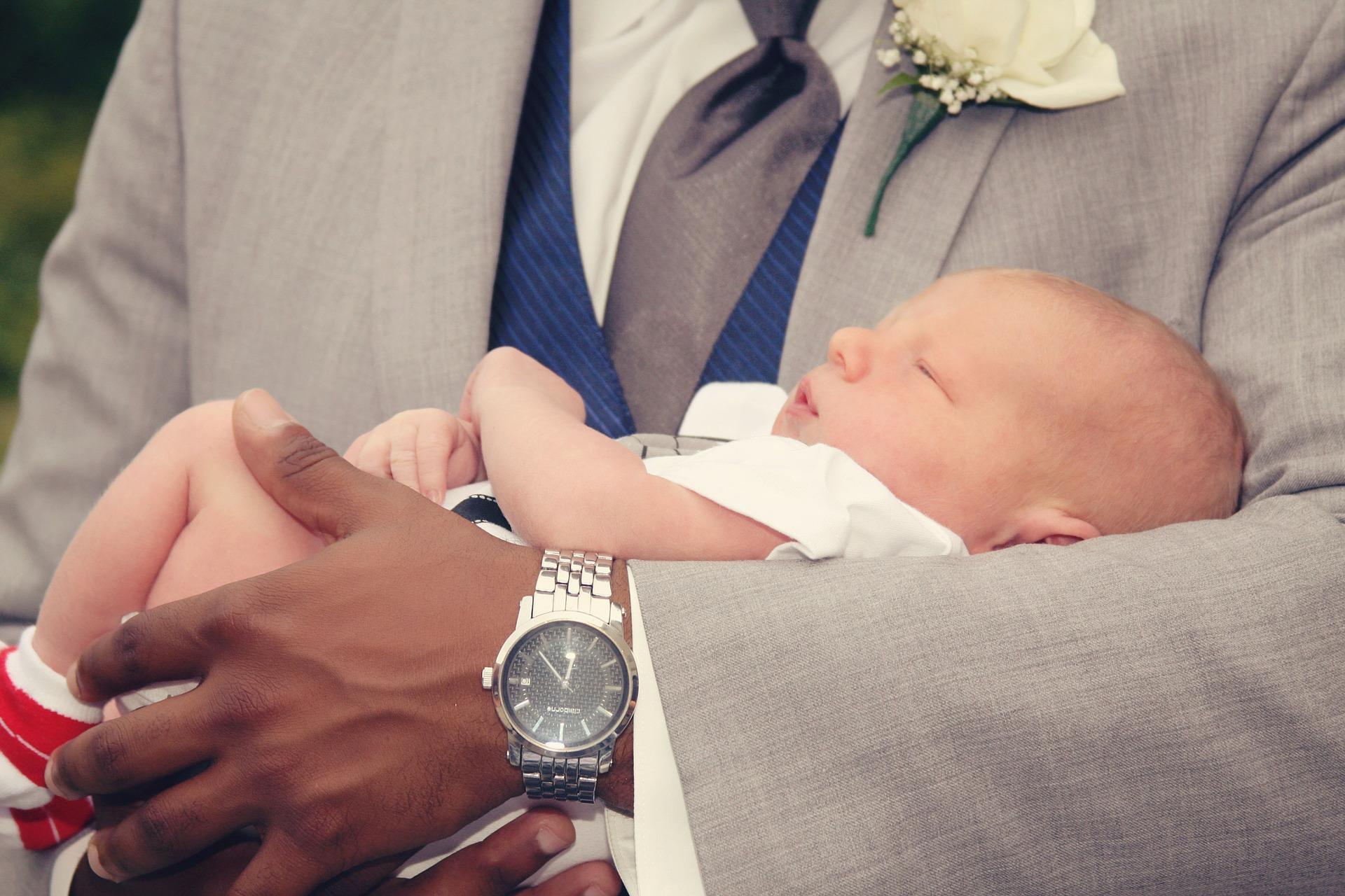 Parrrain tenant son filleul dans les bras