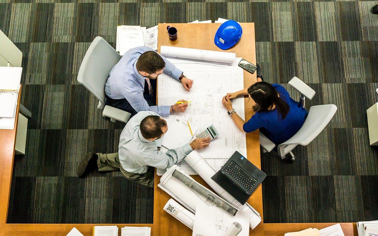 3 personnes en réunion autour d'une table . L'image est prise du plafond